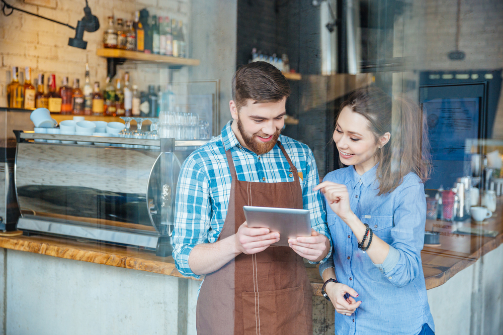 Smiling handsome waiter holding tablet and young pretty woman pointing on it in coffee shop
